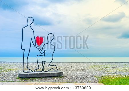 BATUMI GEORGIA - MAY 24 2016: The sculpture of a couple making the love confession on the beach on May 24 in Batumi.
