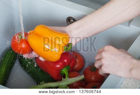 Woman hands washing paprika under the tap