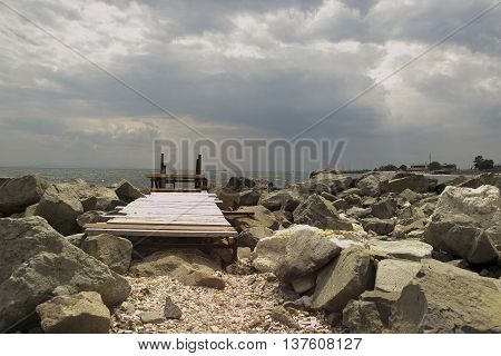 cloudy sky, path to the sea and large stones