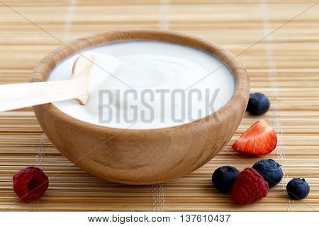 Wooden Bowl Of White Yoghurt With Wooden Spoon Inside On Bamboo Matt. Next To Berries.