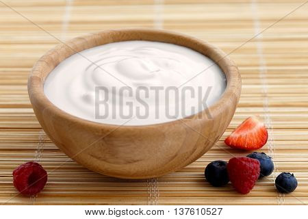 Wooden Bowl Of Fruit Yoghurt On Bamboo Matt Next To Berries.