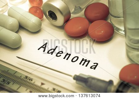 Adenoma - diagnosis written on a white piece of paper. Syringe and vaccine with drugs.
