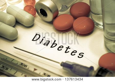 Diabetes - diagnosis written on a white piece of paper. Syringe and vaccine with drugs.