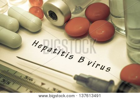 hepatitis B - diagnosis written on a white piece of paper. Syringe and vaccine with drugs