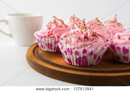 Tea time with pink cupcakes. Birthday cupcake with whipped cream and cup of tea. Homemade cupcakes served on wooden board.