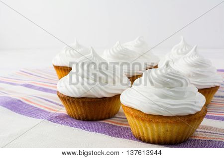White cupcakes on the striped linen napkin close up. Homemade cupcakes with whipped cream. Birthday cupcake.