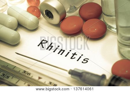 Rhinitis - diagnosis written on a white piece of paper. Syringe and vaccine with drugs.