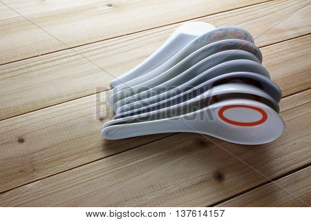 Stack of Chinese Soup Spoons on Wooden Background
