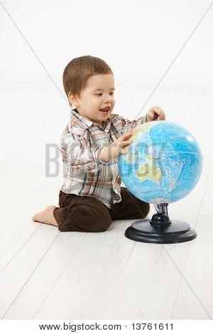Niedlichen kleinen Kind (2-3 Jahre) sitzen auf Boden mit Globus over white Background spielen.?