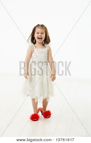 Little daughter trying to walk in mothers big shoes, laughing. Studio shot over white background.?