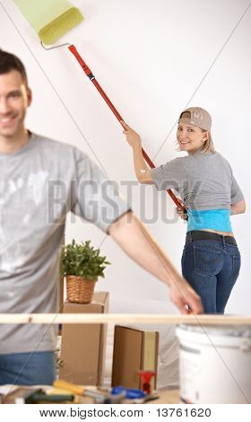 Smiling young woman in focus painting wall with paint roller, man working at table.?