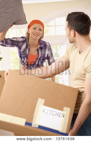 Cheerful woman throwing pillow at man carrying box at moving house.?
