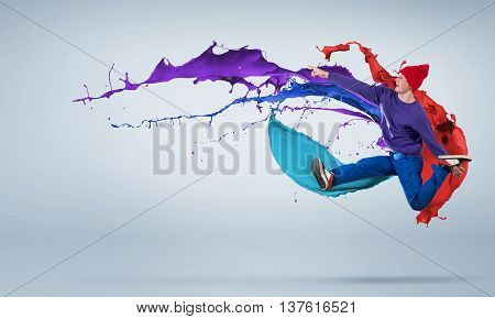 Modern styled dancer jumping over colorful paint splashes