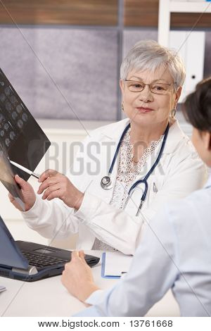 Senior doctor showing scan results to patient in office.?