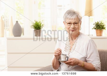 Senior woman drinking coffee in living room, looking at camera smiling.?