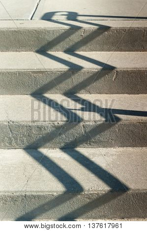 Shadow of railing zigzags up concrete steps
