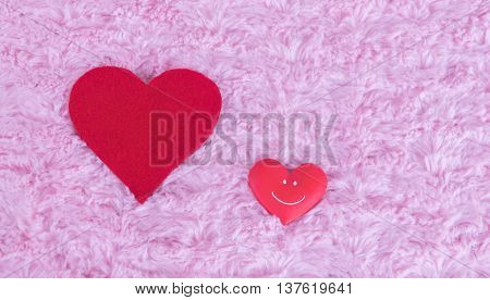 two red hearts of different sizes and one smiles