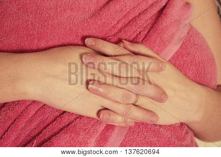 A womans hand on the pink background