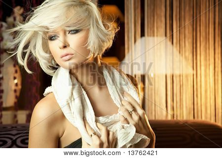 Portrait of beautiful smiling young blond woman relaxing at home