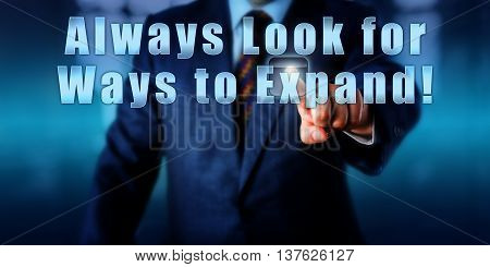 Corporate manager is touching Always Look for Ways to Expand! on an interactive control screen. Business objective concept motivational metaphor and call to action. Close up of torso in suit.