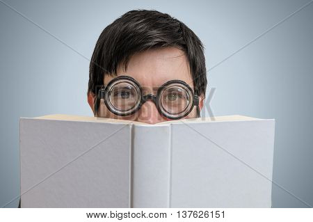 Caucasian Shy Man Is Reading And Is Covering His Face And Is Hid
