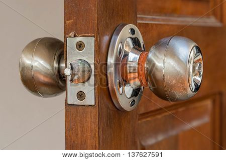 closeup locksmith and silver knob on old wood door need to repair by professional