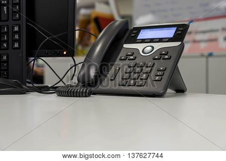 VOIP phone on white desk and near mornitor in office