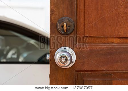 silver knob on old wood door and white car