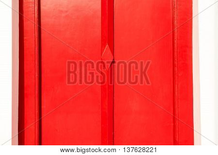 red wood door on white wall at temple
