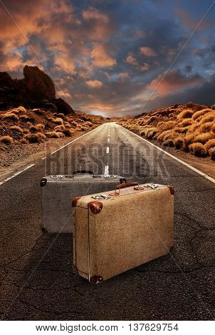 Two vintage suitcases in the middle of a grungy asphalt road leading through desert landscape