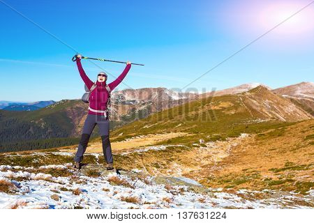 Happy Female Hiker in Sporty Clothing Backpack and walking Poles makes Success gesture raising Hands up european Mountains Scenery View and Sun