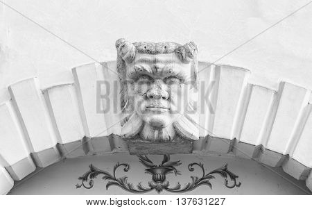 Devil head carved above the entrance arch of an Italian villa.