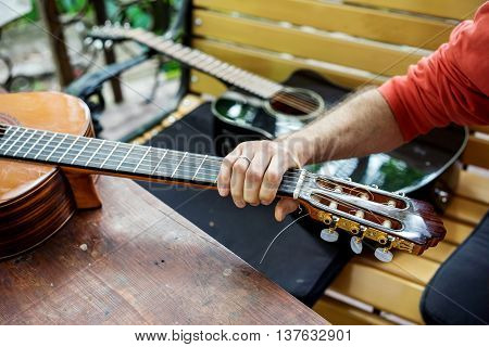 Man takes a classical acoustic guitar in the hand lying on the wooden table