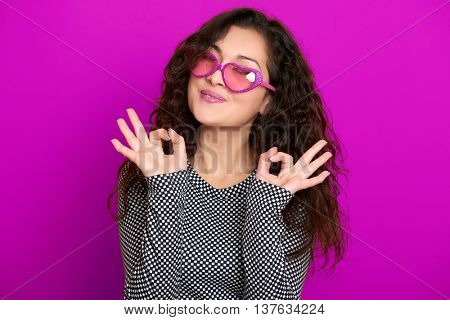 young woman beautiful portrait show okay sign, posing on purple background, long curly hair, sunglasses in heart shape, glamour concept