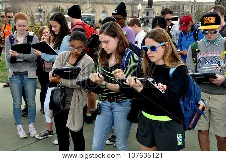 Washington DC - April 9 2014: A group of students on a field trip taking notes while standing in the plaza of the Grant Memorial near the U. S. Capitol