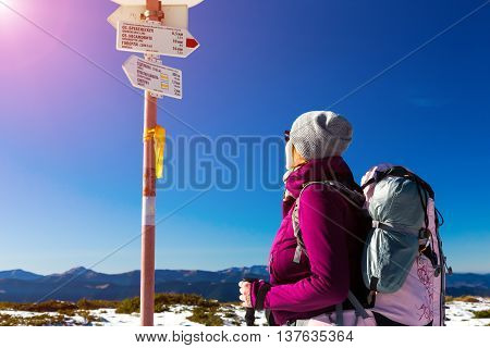 Hiker with Backpack Staying and Looking on Trail Sign sporty Clothing blue Sky