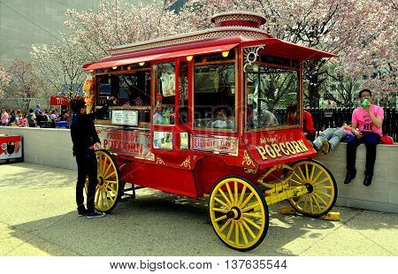 Washington DC - April 11 2014: Popcorn Vendor's classic wagon standing in front of the NASA Museum with its grove of flowering cherry trees