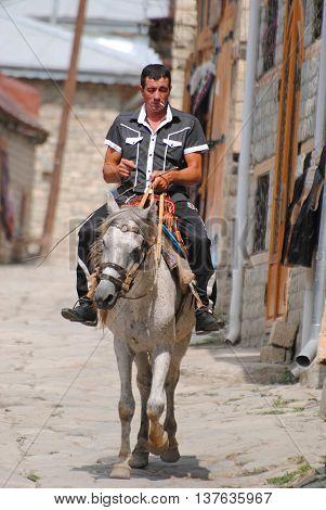 Lahic, Azerbaijan - August 30, 2014. Horse rider on the main street in Lahic mountainous village of Azerbaijan.