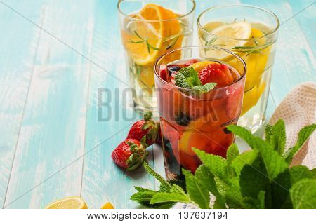 Detox fruit infused flavored water. Refreshing summer homemade cocktail with lemon orange strawberries and blueberries