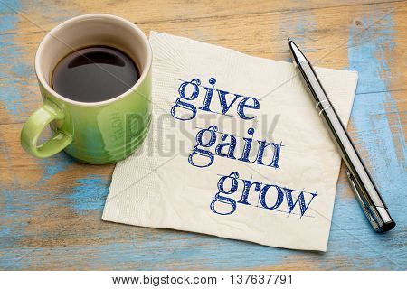 give, gain and grow -personal development concept - handwriting on a napkin with a cup of coffee