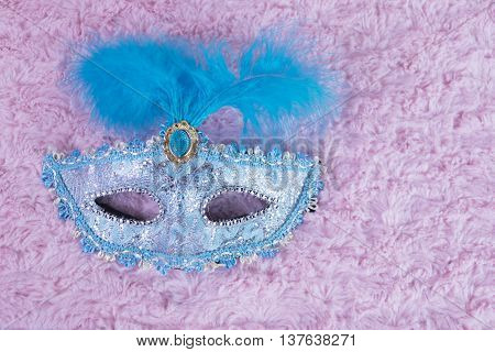 Mask ligth blue with feathers in pink background