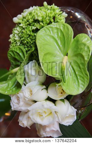 White roses and troppical leafs in a vase