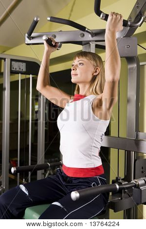 Young woman goes in for sport using the training simulator in the gym