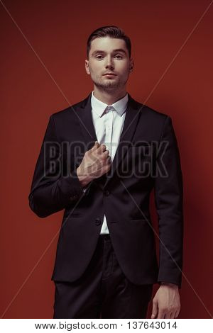 White shirt and black shoes on red background posing