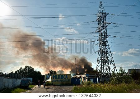 Kiev, Ukraine - June 3 2016: power lines against the background of blue sky and black smoke. A large fire at Troyeschina market