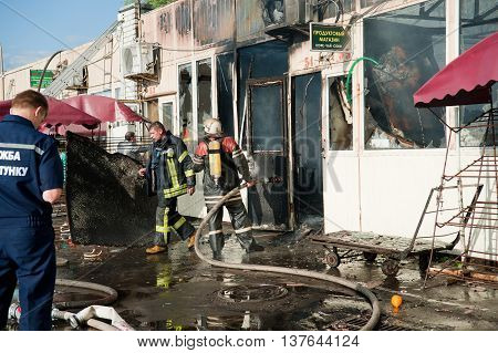 Kiev Ukraine - June 3: Firefighters extinguish a large fire at Troyeschina market with water and fire extinguishers.