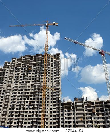 New high-rise modern apartment building construction in process ob bright sunny day front view vertical