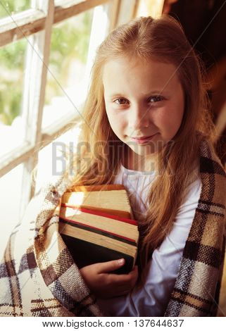 Young beautiful girl with books by the window.