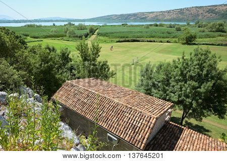 Sas Lake rural scene with back yard field and reedbed, Montenegro