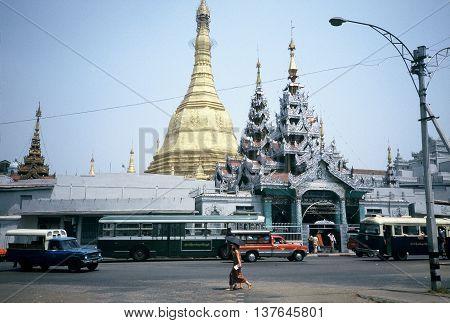 RANGOON / MYANMAR - CIRCA 1987: Traffic circulates past the front entrance of the Sule Pagoda in downtown Rangoon.